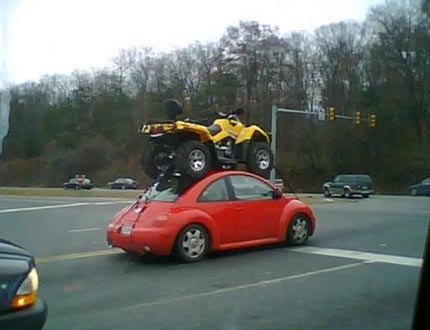 ATV strapped to a VW Beetles roof