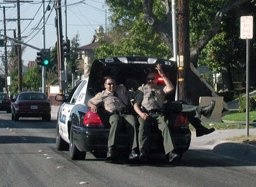 Police Officers Riding In Cop Car Trunk