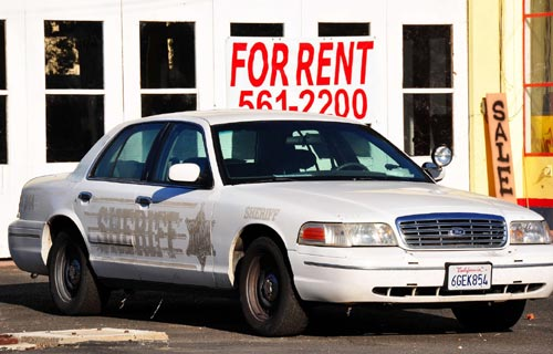 Rent Sign Behind Police Car