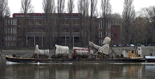 Dismantled Statue Of Lenin Being Transported By Boat With Arm Pointing Straight Ahead